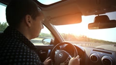 Serious man driving a car at sunset. HD. 1920x1080 Stock Footage