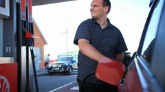 Young serious businessman refueling car tank at fuel station. HD. 1920x1080 Stock Footage