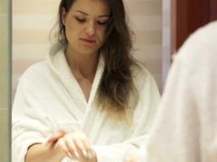Pretty woman in bathrobe applying moisturizing cream on her hands NTSC Stock Footage