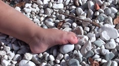 Small baby foot on pebbles- - stock footage