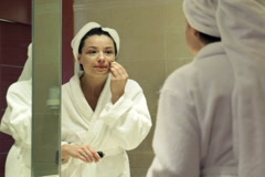 Stock Video Footage of Beautiful woman in bathrobe applying makeup, concealer on her face NTSC