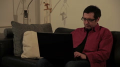 Guy sitting on leather couch, using laptop computer and playing with two balls. Stock Footage