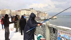 Fisherman trolling rod in snow on the bridge Stock Footage