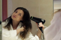 Beautiful, young woman drying her hair in the bathroom NTSC Stock Footage