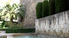Spain Palma de Mallorca 025 gargoyles in a stone wall in city park Stock Footage