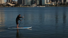 Man On A Stand Up Paddle Board Rows Somewhere Along the San Diego Shore Stock Footage