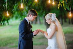 Groom wears the ring bride under the arch Stock Photos
