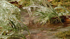 Splashing water frozen grass Stock Footage