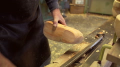 Clog maker cutting of the edges of a clog [SLOMO] Stock Footage
