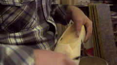 Clog maker is cutting decoration in clog with a gouge - stock footage