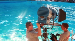 Men set the light fixture in the background of the pool in which dolphins swim Stock Footage