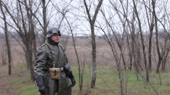 German soldier pulls out a gun from the holster. WW2 reconstruction - stock footage