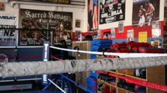 Dolly shot close up of boxing ring ropes and punching bags Stock Footage