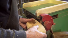 Clog maker drills a hole in the side of clog [Slomo] Stock Footage
