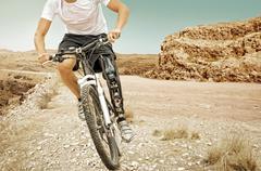 Handicapped mountain bike rider barren landscape - stock photo