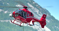 4K Eurocopter Helicopter Hover and Decent in Mountains, Stable Telephoto Shot - stock footage