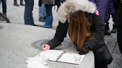 Torontonians sigining to add their voices in paris attacks Stock Footage