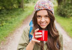 Smiling young woman with cup and backpack hiking Stock Photos