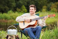 Stock Photo of smiling man with guitar and dixie in camping