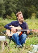 smiling man with guitar and dixie in camping - stock photo