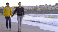 Couple Hold Hands And Walk Along Shoreline, Closeup Of Their Hands Stock Footage