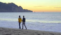 Wide Shot Of Gay Couple Walking Along Shoreline At Sunset Stock Footage