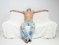 muscular man in torn jeans sitting on the sofa - stock photo