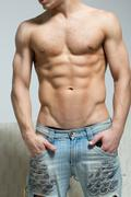 muscular man in torn jeans stands near the sofa - stock photo