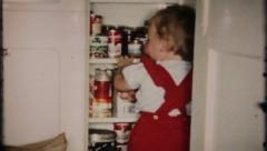 1740 - little girl putting groceries in the cupboard - vintage film home movie - stock footage