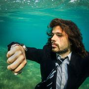 Businessman in Suite Underwater Looking at Watch Portrait Square - stock photo