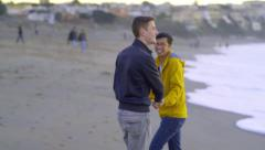 Gay Couple Run Away From Wave On The Beach, They Laugh At Situation Stock Footage
