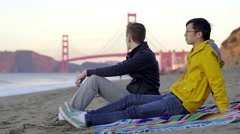 Couple Sit On Picnic Blanket, Then They Get Up And Run Toward Golden Gate Bridge Stock Footage