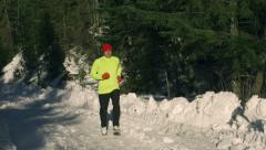 Man running in the forest at winter, steadycam shot, slow motion shot Stock Footage