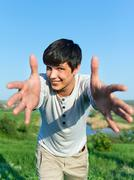 cheerful guy with outstretched arms outdoors - stock photo