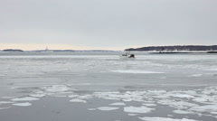 Fishing boat passes through ice chunks in harbor, Portland Maine Stock Footage