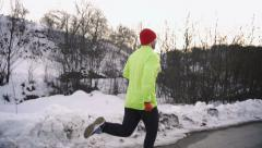 Man jogging and looking back to the camera, steady, slow motion shot at 240fps - stock footage