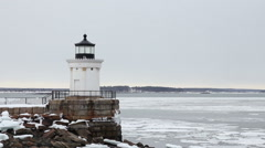 Ice chunks float past Bug Lighthouse, medium shot, South Portland Maine Stock Footage