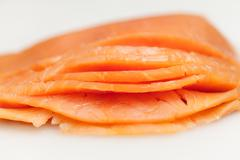 Salmon on white board for sushi preparation - stock photo