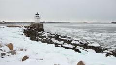 Ice chunks float past Bug Lighthouse, wide shot, South Portland Maine Stock Footage