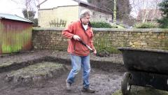Man digging soil then carrying to wheelbarrow. Stock Footage