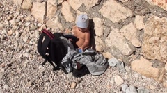 Baby plays with belongings at the beach- Stock Footage