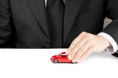 toy car and hand of business man, concept for insurance, buying, renting, fue - stock photo