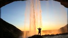Iceland Seljalandsfoss sunset Waterfall mist rock face cliff hiking - stock footage