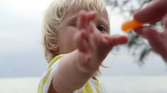 mother gives to little blonde daughter small piece of tangerine - stock footage