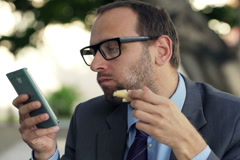 Young businessman with smartphone, eating slice of bread in cafe in city NTSC Stock Footage