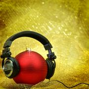 Christmas ball with headphones in glittering background Stock Photos