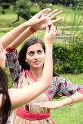 Indian girl learning kathak dance outdoors. - stock photo