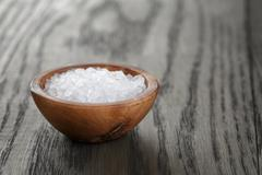 Stock Photo of sea salt in wooden bowl for cooking or spa, on dark table