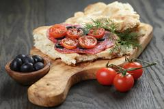 flat pita bread with salami and vegetables on wood table - stock photo