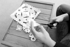 Woman cutting paper into snowflake designs - stock photo